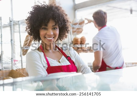Pretty waitress posing with arms crossed at the bakery - stock photo