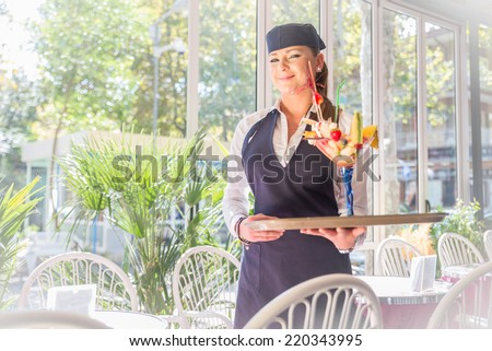 Pretty waitress serving a cup of ice cream in a bar cafe - stock photo