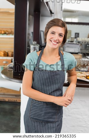 Pretty waitress smiling at camera at the coffee shop - stock photo