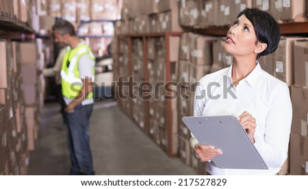 Pretty warehouse manager checking inventory in a large warehouse - stock photo
