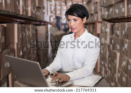 Pretty warehouse manager using laptop in a large warehouse
