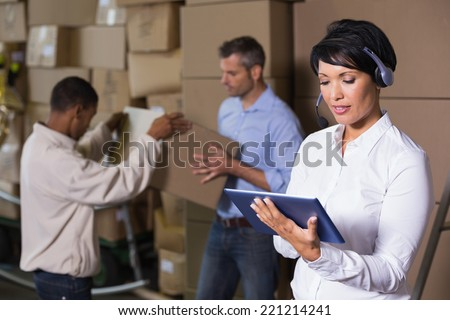 Pretty warehouse manager using tablet during busy period in a large warehouse - stock photo