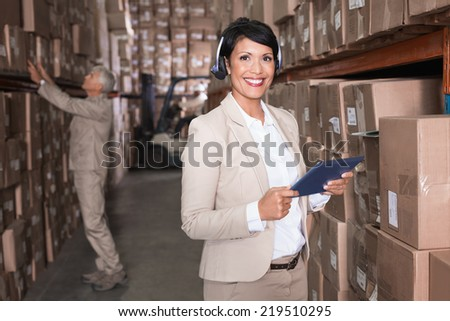 Pretty warehouse manager using tablet pc in a large warehouse