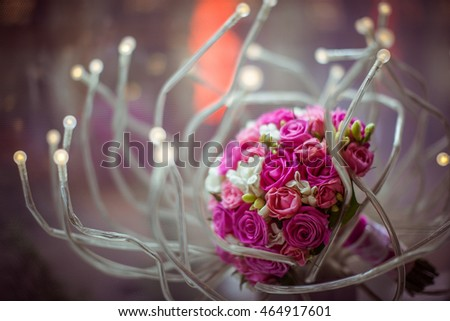 Pretty wedding bouquet lies on the diode lamp