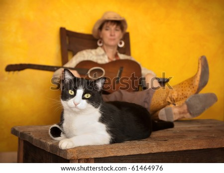 Pretty western woman in antique rocking chair with guitar and cat - stock photo