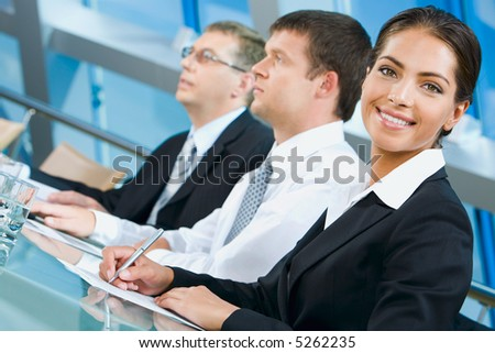Pretty white collar worker is writing a text during business conference
