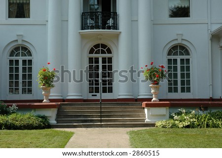 Pretty white grand luxury house / home with two urns with red geraniums - stock photo