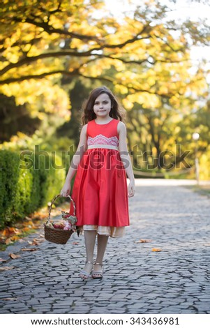 Pretty white little girl with loose dark hair in beautiful red dress and sandals with fruit basket goes on cobbled walkway in day at autumn park, vertical picture - stock photo