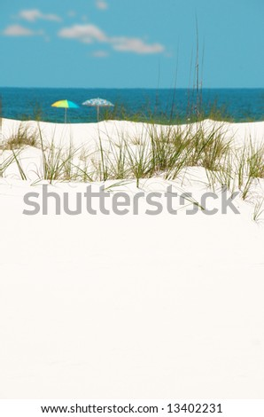 Pretty white sand dune with beach umbrellas by shore in distance - stock photo