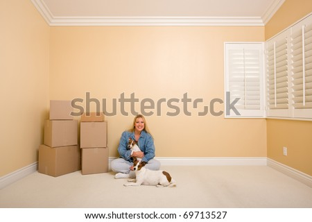 Pretty Woman and Dogs Sitting on the Floor with Moving Boxes in Empty Room - stock photo