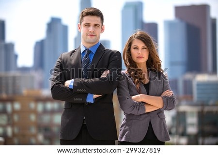 Pretty woman and handsome businessman posing with serious expression determined for success - stock photo