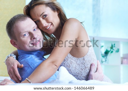 Pretty woman and her husband embracing and looking at camera