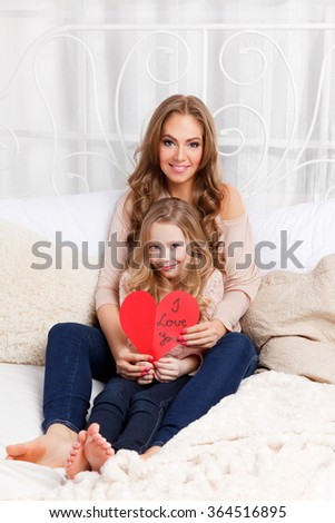Pretty woman and little girl holding a cardboard heart - stock photo