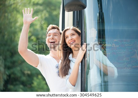 Pretty woman and man are standing in doors of the bus. They are looking through it and laughing. The boy is raising his palm and helloing with everybody - stock photo
