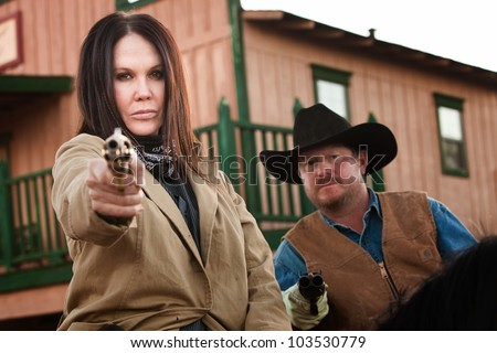 Pretty woman and partner aim guns in old west town - stock photo