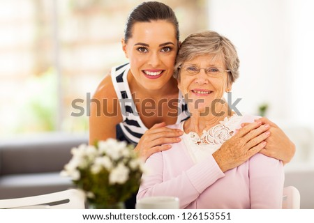 pretty woman and senior mother at home - stock photo