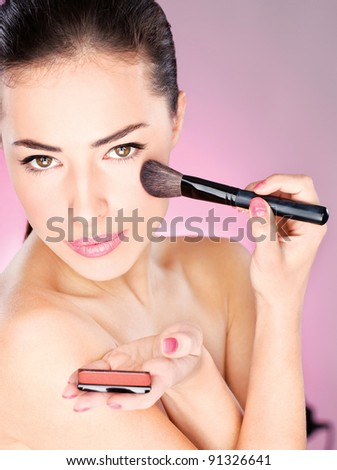pretty woman applying cosmetic powder brush