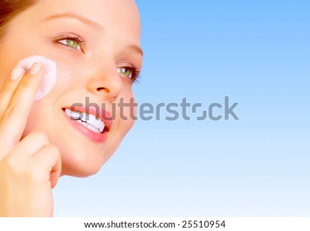 Pretty woman applying cream. Over blue background - stock photo