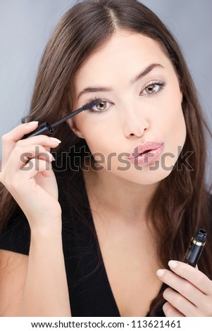 pretty woman applying mascara