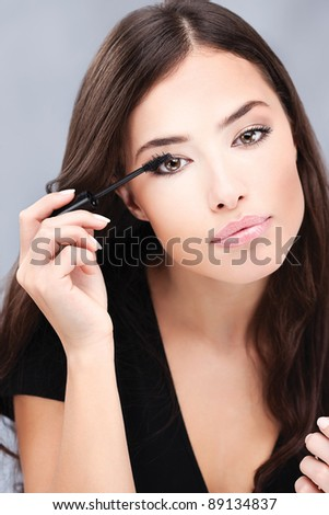 pretty woman applying mascara on her lashes
