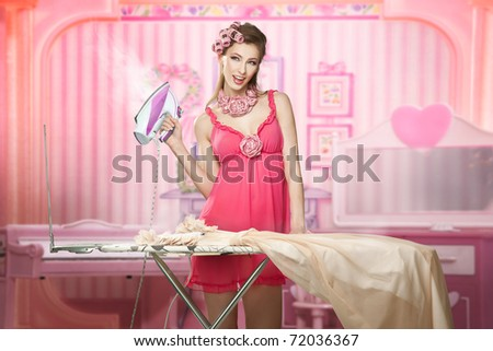 Pretty woman as a doll doing house work - stock photo