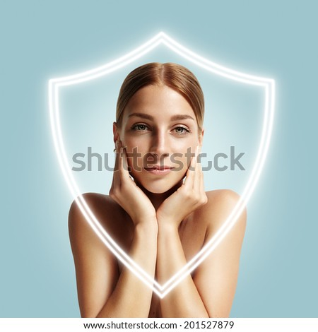 pretty woman behind a shield which safe her skin - stock photo