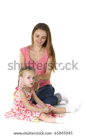 Pretty woman brushing her daughter's hair against a white background
