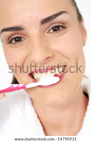 Pretty woman brushing her teeth