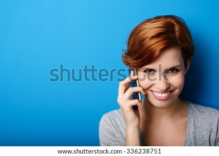 Pretty Woman Calling Someone Through Mobile Phone While Smiling at the Camera Against Blue Wall Background with Copy Space. - stock photo