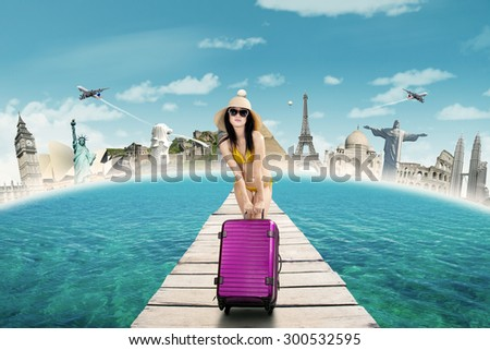 Pretty woman carrying luggage and wearing bikini on the bridge to enjoy the journey to the worldwide monument - stock photo