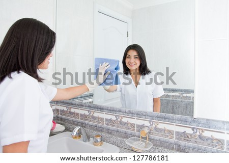 Pretty woman cleans  mirror in bathroom at home - stock photo
