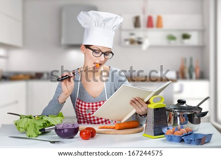 Pretty woman cooking with cookbook - stock photo