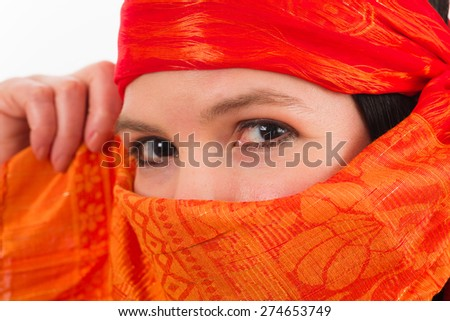 Pretty woman covered by a orange colored veil on a white background. - stock photo