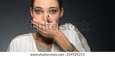 Pretty woman covering mouth with hands. Speak no evil concept. - stock photo