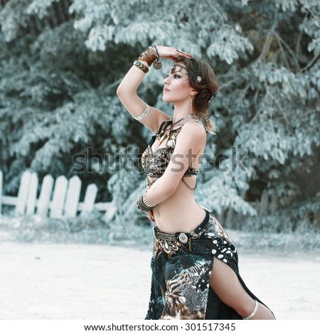 Pretty woman dancing in the tribal style on the background of fabulous trees. - stock photo
