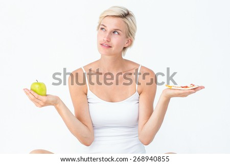 Pretty woman deciding between pizza and apple on white background - stock photo