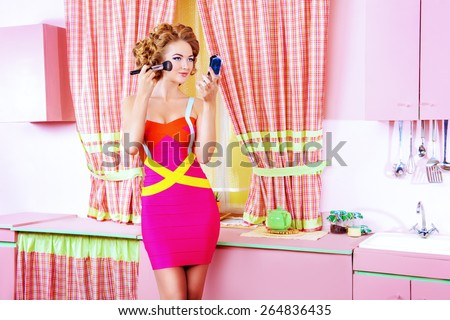 Pretty woman doing makeup on her glamorous pink kitchen at home. Beauty, fashion. - stock photo