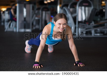 Pretty woman doing push-ups in the gym - stock photo