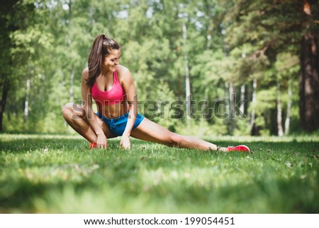 Pretty woman doing sport exercises in the outdoor - stock photo