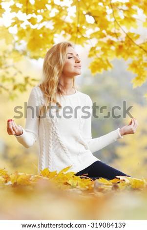 Pretty woman doing yoga exercises in autumn park - stock photo