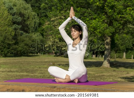Pretty woman doing yoga exercises in the park. - stock photo
