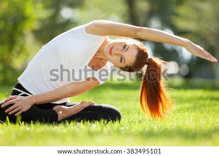 Pretty woman doing yoga exercises in the park - stock photo