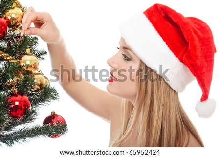 Pretty woman dressed as Santa Claus is standing beside a fir tree, smiles happy and holds a glass ball in her hand. Isolated on white background. - stock photo