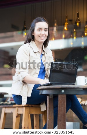 Pretty woman drinking coffee in the street