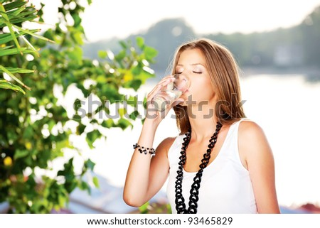 Pretty woman drinking glass of water - stock photo