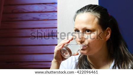 Pretty woman drinking water at home - stock photo