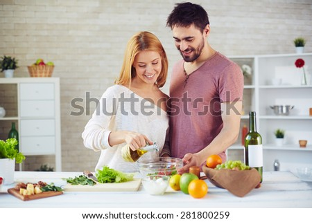 Pretty woman dripping olive oil into salad with her husband near by - stock photo