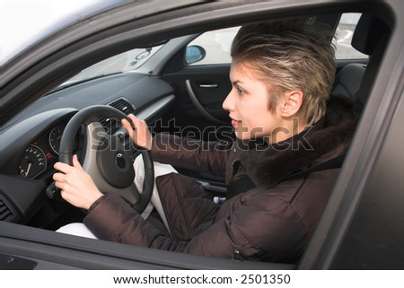 pretty woman driving a car hands on the wheel - stock photo