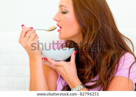 Pretty woman eating muesli at home