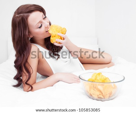 pretty woman eating potato chips in bed at home - stock photo